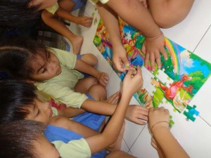 Children helping each other to complete the puzzle.