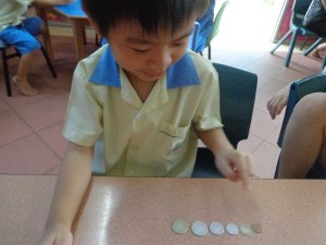 Gavin arranging coins according to the size.