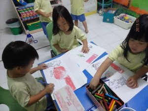 Children are making a poster about the things they love about Singapore to celebrate her birthday.